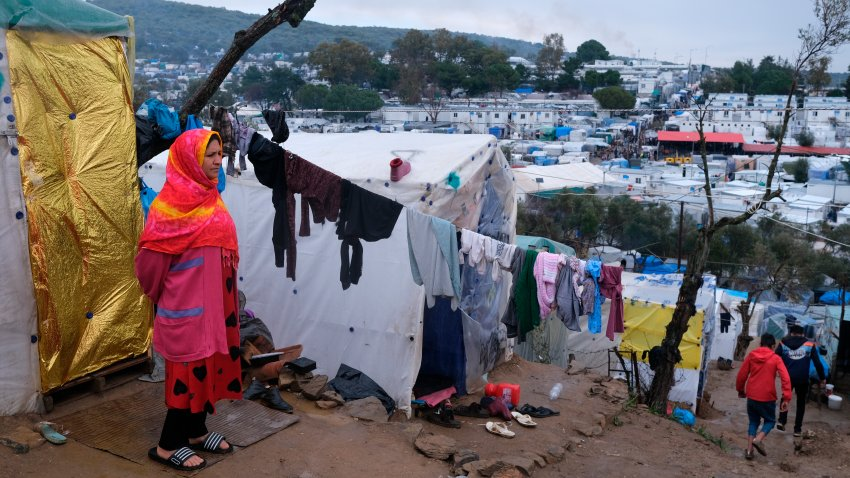In this file photo, a migrant stands next to their makeshift tent outside the perimeter of the overcrowded Moria refugee camp on the northeastern Aegean island of Lesbos, Greece, Wednesday, March 11, 2020.