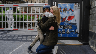 Janis Mackey Frayer and her son hug.