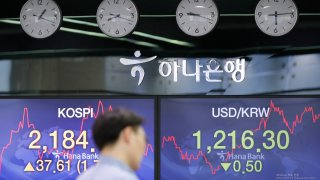In this June 4, 2020, file photo, a currency trader walks by the screens showing the Korea Composite Stock Price Index (KOSPI), left, and the foreign exchange rate between U.S. dollar and South Korean won at the foreign exchange dealing room in Seoul, South Korea.