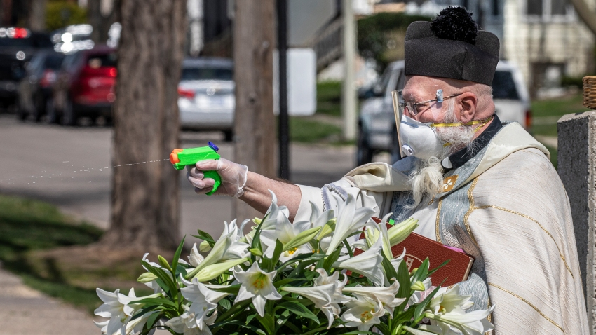 Father Tim Pelc squirts parishioners with his water gun.