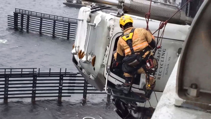 In this Monday, April 13, 2020, photo provided by the Chesapeake Fire Department, a Chesapeake firefighter tries to rescue the driver of a tractor trailer on the High Rise Bridge over the Elizabeth River, in Chesapeake, Va.