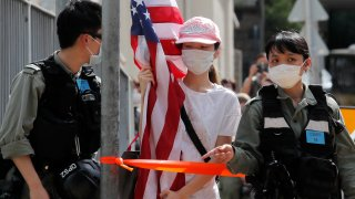 """A protester carrying an American flag as she is stopped by riot police during a protest outside the U.S. Consulate in Hong Kong, Saturday, July 4, 2020 to mark the American Independence Day or """"the Fourth of July."""""""