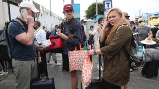 Tourists from the United States wait outside the closed Jorge Chavez International Airport in Callao, Peru