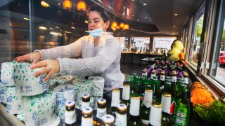 Sarah Rivas, an employee at Annie's Paramount Steakhouse in the Dupont Circle area of Washington, D.C., arranges a display of toilet paper and liquor for carry out orders Monday, April 13, 2020.
