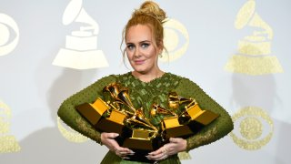Adele poses with the five awards she won at the 59th Grammy Awards