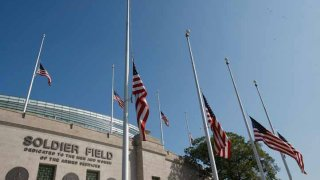 American Flags are flown at half mast outside Soldier Field