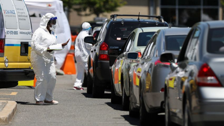 Medical workers take down personal information from those driving in to take a COVID-19 test at a Coronavirus testing location in the Cambridge Health Alliance Testing Tent in Cambridge, MA on June 18, 2020. Massachusetts has launched more than 50 pop-up coronavirus test sites to provide free testing for people who participated in large gatherings or protests.