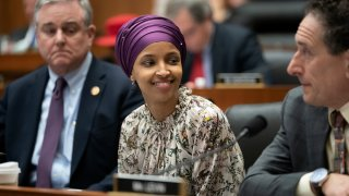In this file photo, Rep. Ilhan Omar, D-Minn., sits with fellow Democrats, Rep. David Trone, D-Md., left, and Rep. Mike Levin, D-Calif., right, on the House Education and Labor Committee during a bill markup, on Capitol Hill in Washington, Wednesday, March 6, 2019.