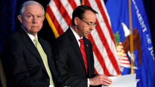 In this June 10, 2017, file photo, Attorney General Jeff Sessions, left, and Deputy Attorney General Rod Rosenstein take their seats at the Justice Department's National Summit on Crime Reduction and Public Safety, in Bethesda, Md.