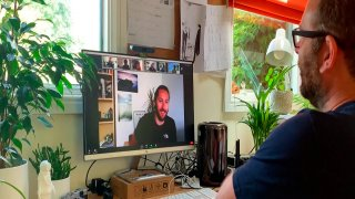 This July 2020 photo taken from video released by Locksmith Animation shows art director Justin Hutchinson-Chatburn, right, communicating on his computer during the filming of a video diary