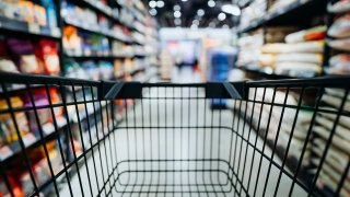 Personal perspective of a shopper pushing shopping trolley along product aisle while shopping in a supermarket