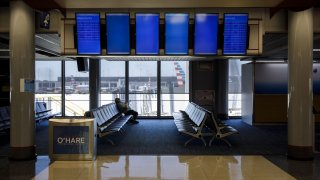A passenger sits beneath a nearly empty departures board in the American Airlines Group Inc. at O'Hare International Airport (ORD) in Chicago