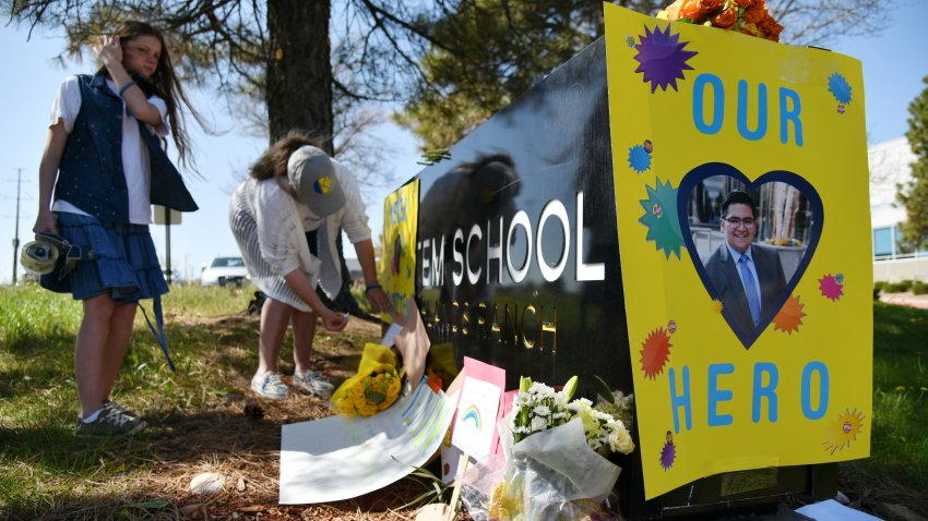 Sydney Monteith, left, and her mother Jennifer place the poster of Kendrick Castro on the STEM School Highlands Ranch. Students and parents car rally for one year memorial of STEM School Highlands Ranch shooting in Highlands Ranch, Colorado on Thursday. May 7, 2020.