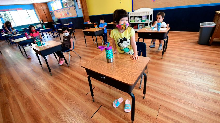 Children in a pre-school class wear masks and sit at desks spaced apart as per coronavirus guidelines during summer school sessions in Monterey Park, California on July 9, 2020. - California Governor Gavin Newsom says the reopening of California schools for the coming school year will be based on safety and not pressure from President Donald Trump as California sets records for one-day increases in COVID-19 cases.