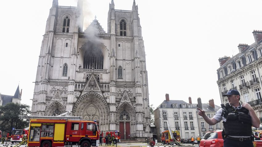 "A French Police officer gestures as firefighters are at work to put out a fire at the Saint-Pierre-et-Saint-Paul cathedral in Nantes, western France, on July 18, 2020. - The major fire that broke out on July 18, 2020 inside the cathedral in the western French city of Nantes has now been contained, emergency services said. ""It is a major fire,"" the emergency operations centre said, adding that crews were alerted just before 08:00 am (0600 GMT) and that 60 firefighters had been dispatched."