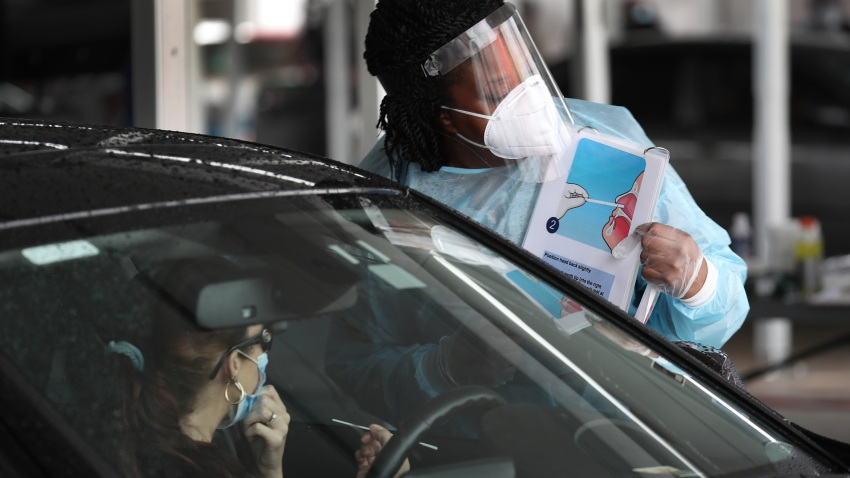 A health care worker uses a picture to show a person how to use a nasal swab for a self administered test at the new federally funded COVID-19 testing site at the Miami-Dade County Auditorium on July 23, 2020 in Miami, Florida. Vice Admiral Jerome Adams, the U.S. Surgeon General, visited the site, as the state of Florida experiences a spike in coronavirus cases, to encourage people to wear a mask and take other precautions to fight the pandemic.