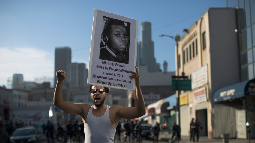 LOS ANGELES, CA - OCTOBER 22: Nick Keen participates in the ''National Day of Protest to Stop Police Brutality, Repression and the Criminalization of a Generation'' in the Skid Row area October 22, 2015 in Los Angeles, California. Keen holds a poster showing Michael Brown, who was killed by Ferguson police in 2014. Activists are marching in Los Angeles, New York City and some 30 other cities today to protest alleged police brutality.