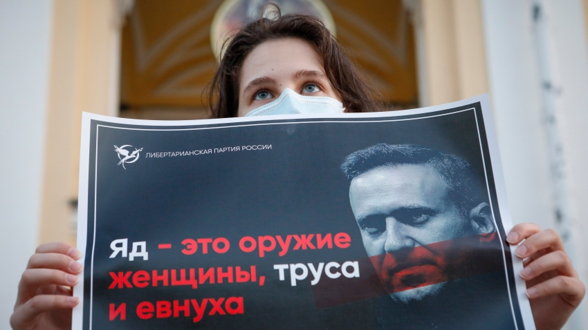 "A protester stands holds a poster reads ""poison is the weapon of a woman, a coward and a eunuch!"" during a picket in support of Russian opposition leader Alexei Navalny in the center of St. Petersburg, Russia, Thursday, Aug. 20, 2020. Russian opposition politician Alexei Navalny is on a hospital ventilator in a coma, after falling ill from a suspected poisoning, according to his spokeswoman Kira Yarmysh."