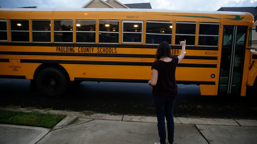 Rachel Adamus waves goodbye to her two children, Paul and Neva, as they ride the bus for the first day of school on Monday, Aug. 3, 2020, in Dallas, Ga.