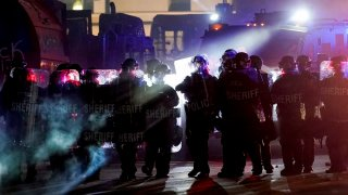 authorities disperse people from a park in Kenosha, Wis
