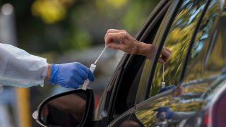 A public health worker receives a test swab from a patient at a COVID-19 testing site in Martinez, Calif., Aug. 4, 2020.