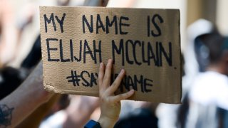 AURORA, CO - JUNE 27: A woman holds up a sign as people rally outside the Aurora Police Department Headquarters to demand justice for Elijah McClain on June 27, 2020 in Aurora, Colorado. On August 24, 2019 McClain was walking home when he was forcibly detained by three Aurora police officers and was injected with ketamine after officers requested assistance from the Aurora Fire Rescue. McClain suffered a heart attack on the way to the hospital that night and died six days later.