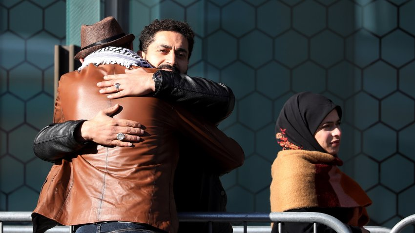 Survivors and family members of the 2019 twin mosque shootings greet each other outside the High Court building on the last day of the sentencing hearing for Brenton Tarrant, the gunman who massacred 51 people during the attacks, in Christchurch on August 27, 2020.