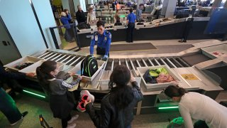 Officials from the Transportation Security Administration and Massachusetts Port Authority introduce the new automated screening lanes at Logan Airport's Terminal C in Boston on Dec. 20, 2017
