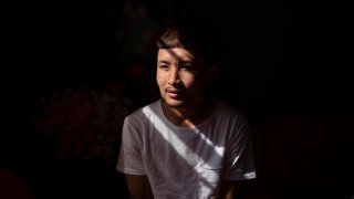 """Bawi UK, 22, is photographed in his apartment in Providence, R.I., Saturday, Sept. 26, 2020. UK was a small child when his parents fled Myanmar, leaving him and his siblings to be cared for by their maternal grandmother. UK said the family suffered discrimination as Christians in a predominantly Buddhist nation. The military government was also trying to forcibly conscript his father. """"To run for office, you had to be a Buddhist; to rent a house, you had to be Buddhist,"""" said UK, a social work student at Rhode Island College and a youth leader at the Refugee Dream Center, an advocacy organization in Providence."""