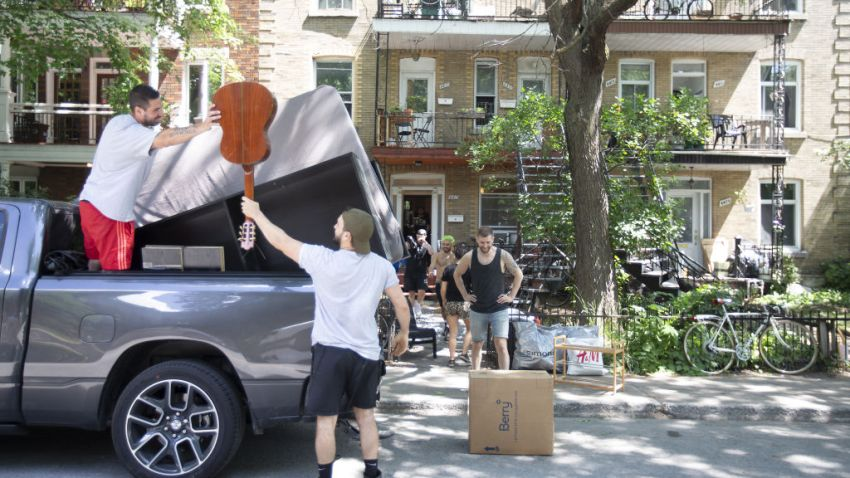 A group of people unload household items from a truck in Montreal, Quebec, Canada, on Wednesday, July 1, 2020. On the city's traditional moving day, local companies are trying to make up for some of the income lost during the Covid-19 shutdown with a big July 1 push, CTV News reports.