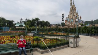 A visitor sits at a bench next to a white cord as he waits for the park to be open at the Disneyland Resort in Hong Kong, China on September 25, 2020.