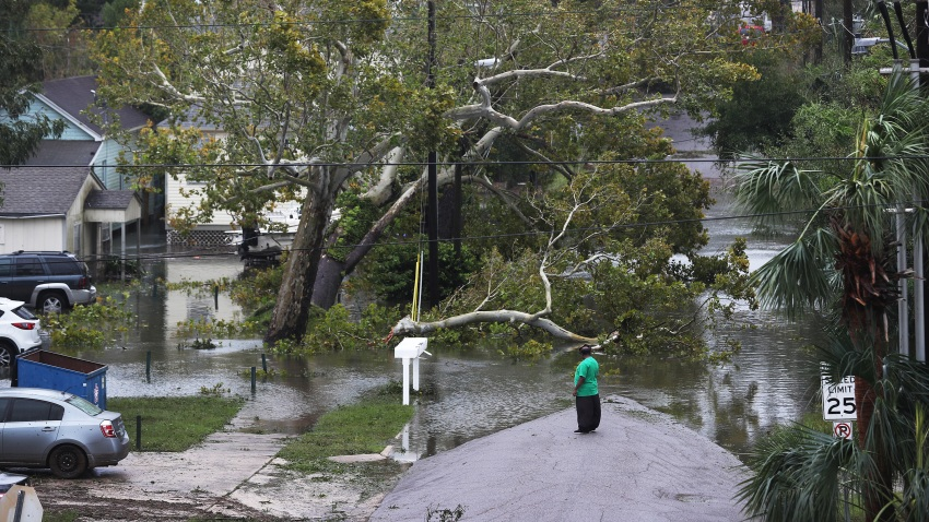 A person looks at a flooded neighborhood as Hurricane Sally passes through the area on September 16, 2020 in Pensacola, Florida. The storm is bringing heavy rain, high winds and a dangerous storm surge to the area.