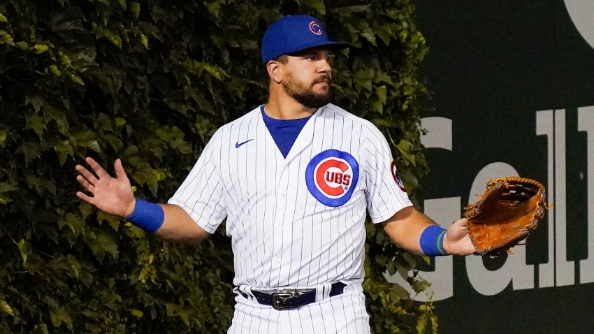 Kyle Schwarber holds up his hands after losing a ball in the ivy at Wrigley Field