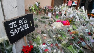 """A poster reading """"I am Samuel"""" and flowers lay outside the school where slain history teacher Samuel Paty was working, Saturday, Oct. 17, 2020 in Conflans-Sainte-Honorine, northwest of Paris"""
