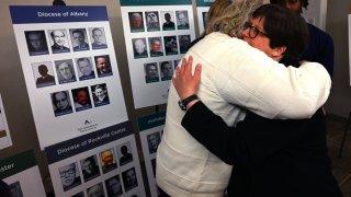 Survivor Bridget Lyons hugs a man after a press conference in New York