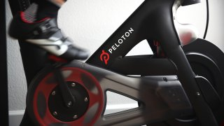 Cari Gundee rides her Peloton exercise bike at her home
