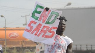"""A protester holds a sign reading """"End SARS"""""""