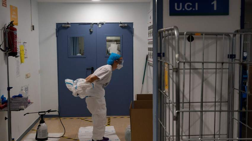 A healthcare worker takes off her protective suit after attending to coronavirus patients at the Intensive Care Unit (ICU) of the Severo Ochoa University Hospital in Leganes on October 16, 2020.