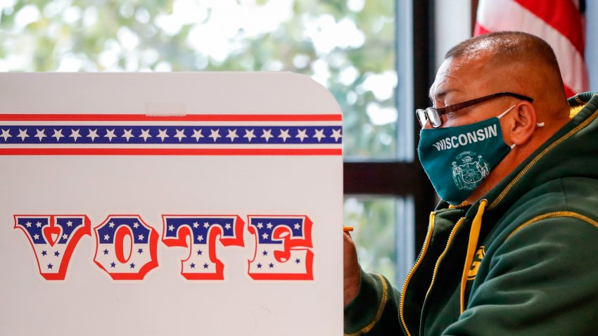 In this Oct. 20, 2020, file photo, a man casts his ballot at Tippecanoe Library on the first day of in-person early voting for the November 3rd elections in Milwaukee, Wisconsin.