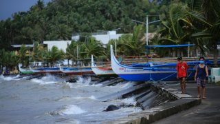 Residents walk past parked wooden boats along a boulevard in Legaspi, Albay province, south of Manila on October 31, 2020, ahead of Typhoon Goni's landfall.