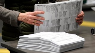 An election worker sorts mail-in ballots at the Multnomah County Duniway-Lovejoy Elections Building Monday, Nov. 2, 2020, in Portland, Ore.