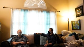 Nicholas Philbrook, right, talks to his father-in-law, Raymond Schmidt, at home