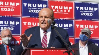 Attorney for the President, Rudy Giuliani, speaks at a news conference with Trump election posters in the background.