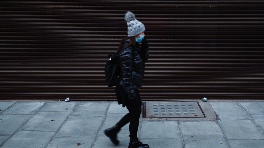 A woman wearing a face mask walks past a temporarily-closed store