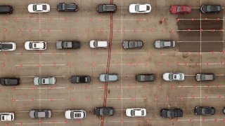 This aerial view shows people waiting in line in their cars at a Covid-19 testing site at Dodger Stadium
