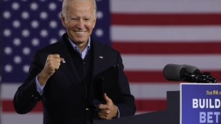 Joe Biden smiles while holding up a hand in front of an American flag.