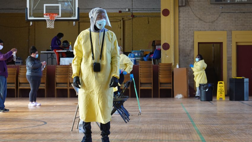 A worker helps residents perform COVID-19 tests at a test site run by CORE at St. Benedict the African Catholic Church in the Englewood neighborhood