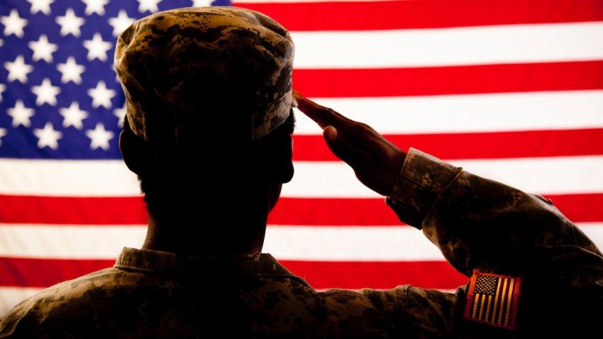 A military veteran salutes the American flag.