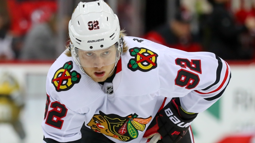 Blackhawks forward Alex Nylander, wearing a white Blackhawks jersey with a white helmet, awaits a faceoff against the New Jersey Devils