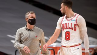 Bulls head coach Billy Donovan, wearing a gray shirt and black pants, and Zach LaVine, wearing the team's white home jersey and shorts, walk and talk during a game against the Rockets